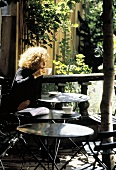 A Woman Sitting at a Table Drinking Coffee