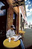 A Man Sitting Outside a Coffee Shop Reading a Newspaper