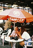 Two Women Sitting at an Umbrella Table; Coffee Shop