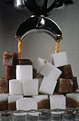 Kaffee fliesst aus Maschine auf Zuckerwürfel
