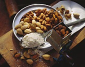 Whole and Shelled Almonds on a Plate; Ground Almonds on a Spoon