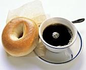Ein Bagel auf Papier & eine Tasse schwarzer Kaffee