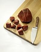 A Piece of Beef Half Chopped on a Cutting Board
