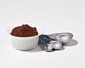 Cocoa Powder in a Bowl with Metal Measuring Spoons