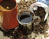 A Cup of Coffee with Coffee Beans and Ground Coffee