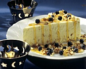 A Slice of Mousse Cake with Blueberries Orange Sauce and Nuts