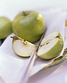 A Cut Granny Smith Apple; Knife