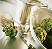 Artichokes in and Beside a Strainer; Kitchen Utensils