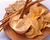 Cheese dip with crisps, salted sticks & crackers on wooden board