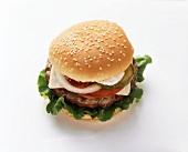 Cheeseburger mit Tomaten, Zwiebeln etc. auf hellem Untergrund