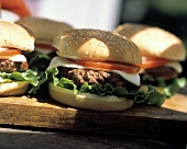 Mehrere Cheeseburger im Freien auf einem Holzbrett