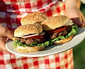 Person Holding a Plate with Three Hamburgers