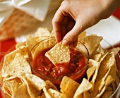 Hand Dipping a Tortilla Chip into Salsa