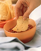 A Hand Dipping a Chip into a Bowl of Salsa