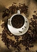 Kaffebohnen in der Tasse und verstreut
