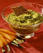 A Cracker Dipped in Pea Yogurt Dip; Carrots