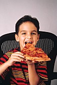 Young Boy Eating Cheese Pizza
