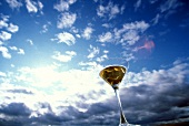 Martini mit Oliven in einem Glas vor blauem Himmel mit Wolken