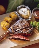 Partially Sliced Rib Eye Steak with Corn on the Cob
