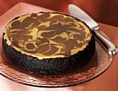 Chocolate peanut butter swirl cheesecake on glass plate