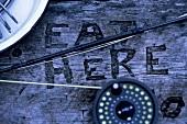 Angel auf verwittertem Holztisch mit Schrift (Eat Here)
