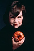 Boy Dressed for Halloween Eating a Donut
