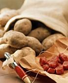 Rindfleischwürfel auf Papier und Kartoffeln aus einem Sack
