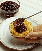 Spreading Apple Blueberry Jam on an English Muffin