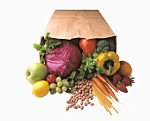 Vegetables, fruit, herbs and pasta in a paper bag