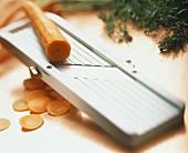 Eine Möhre auf Gemüsereibe und Möhrenscheiben
