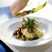 Pouring Oil Over Polenta Topped with Wild Mushrooms