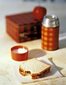 A Lunchbox; Thermos; Peanut Butter and Jelly Sandwich
