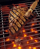 T-Bone Steak on the Grill with Barbecue Brush