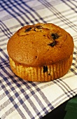 Single Blueberry Muffin on Blue and White Dish Cloth