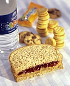 Half of a Peanut Butter and Jelly Sandwich with Crackers and Water