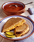 A Grilled Cheese Sandwich with Two Pickle Slices and Tomato Soup