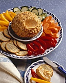 A Cheese Ball with Sliced Vegetables and Crackers