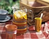 A Pitcher of Iced Tea by a Picnic Basket