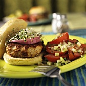 A Turkey Burger with Red Onions and Sprouts