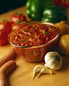 Tomato salsa in glass bowl; fresh vegetables; sausages