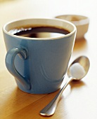 Black Coffee in a Blue Mug with Spoon and Sugar Cube