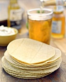 A Stack of Flour Tortillas with a Glass of Beer