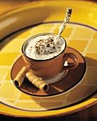 Cappuccino in brauner Tasse mit Hippenröllchen
