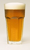 A glass of beer with a head of froth