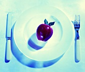 A Red Delicious Apple on a Plate; Fork and Knife