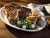 A T-Bone Steak with Crisp Potato Wedges,Snow Peas and Pearl Onions