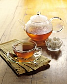 A Glass Teapot, Cup and Saucer with Sugar Cubes