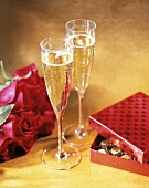Two Flutes of Champagne, Roses and Candy on Gold Background