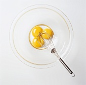Three Egg Yolks in a Bowl with a Whisk