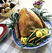 A Whole Roast Turkey on a Platter Garnished with Herbs and Fresh Vegetables